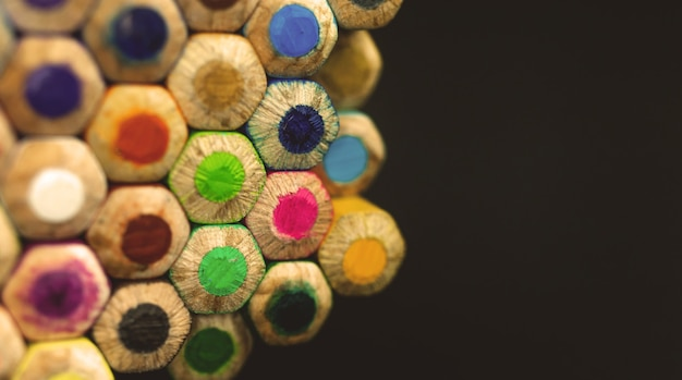 Pilha de lápis de desenho colorido no fundo preto isolado com espaço de cópia, close-up e foto de foco seletivo