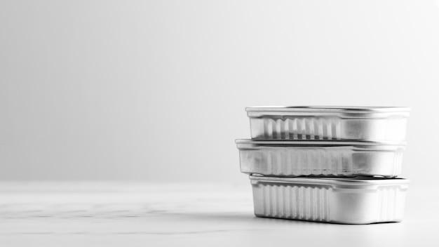 Pilha de latas prateadas de frente com espaço de cópia