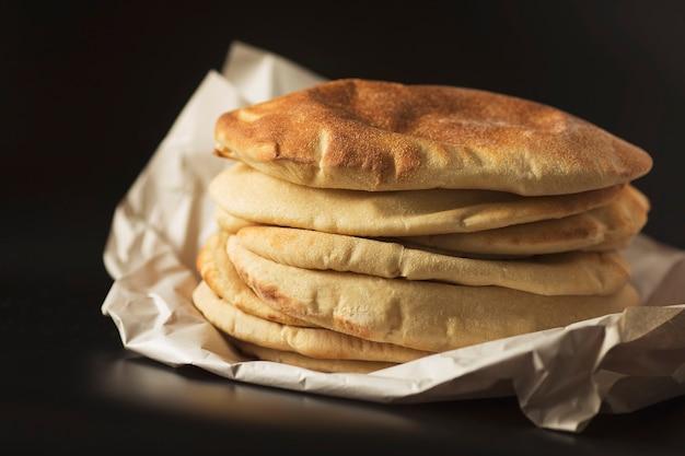 Pilha de lavash de pão pita, lavash de pão sírio caseiro tradicional oriental tradicional, chipre, pão turco, sobre o fundo preto.