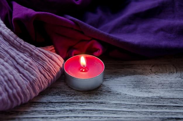 Pilha de lenços confortáveis e uma vela acesa no escuro