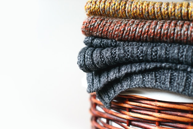 Pilha de lenços de inverno tricotados em uma cesta de palha isolada
