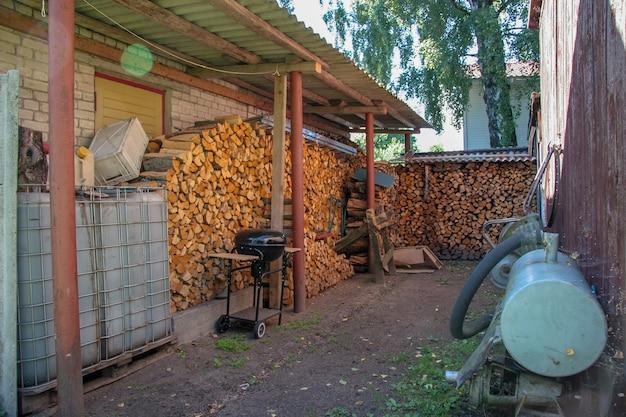Pilha de lenha na parede da casa com churrasqueira e tanque de água. a lenha é coberta com um telhado. a caixa e as latas mentem. pendure o aro das rodas. atrás da cerca cresce uma espessa bétula.