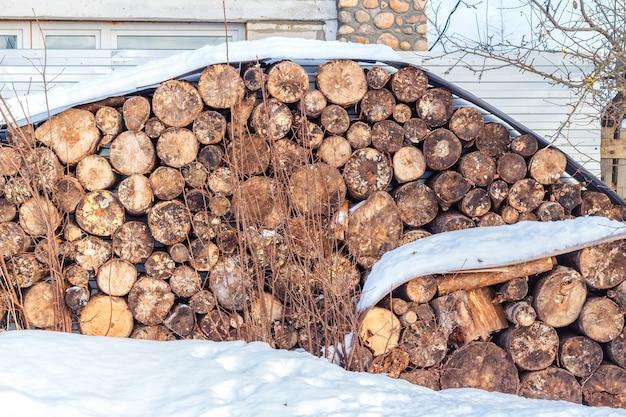 Pilha de lenha sob a neve no inverno. aquecimento natural da casa