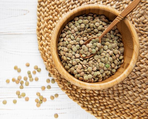 Pilha de lentilha crua em uma tigela na superfície de madeira branca