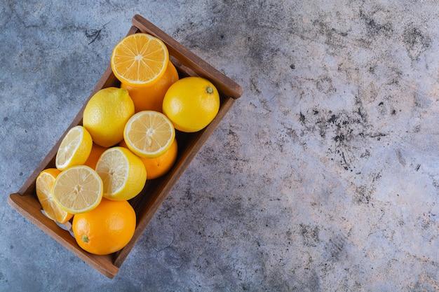 Pilha de limões e laranjas orgânicos em caixa de madeira.