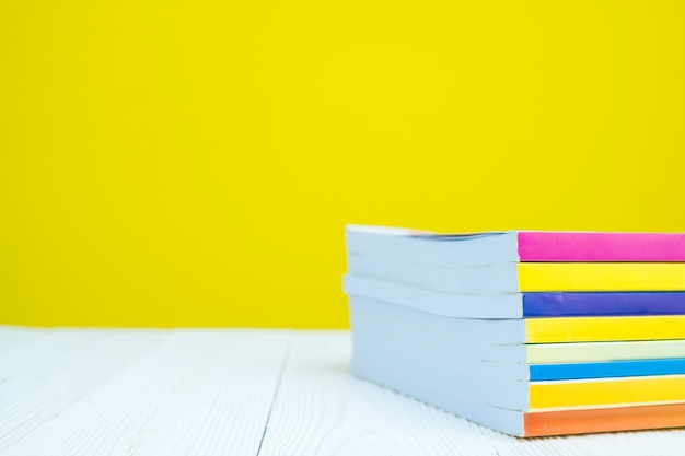 Pilha de livro na mesa branca com amarelo.