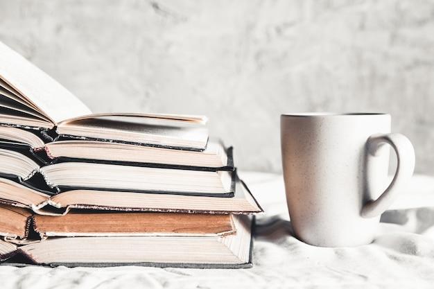 Pilha de livros abertos com uma xícara de café na cama