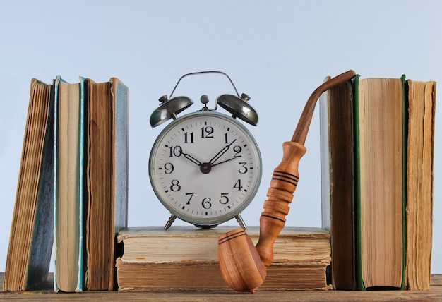 Pilha de livros antigos, cachimbo e despertador na prateleira de woden contra a parede branca