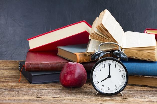 Pilha de livros antigos com despertador antigo e maçã na prateleira de madeira
