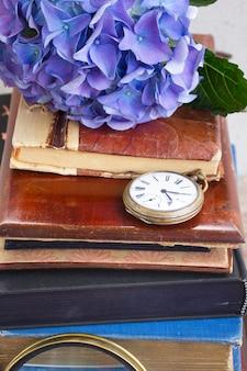 Pilha de livros antigos com flores azuis de hortênsia e um relógio de bolso antigo