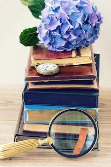 Pilha de livros antigos com flores azuis e um relógio de bolso antigo