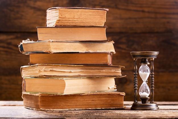 Pilha de livros antigos e ampulheta retrô em fundo de madeira