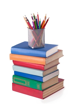 Pilha de livros antigos e lápis de cor isolados no branco