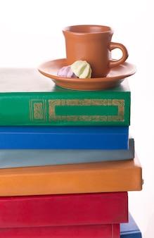 Pilha de livros antigos e uma xícara de café isolado no branco