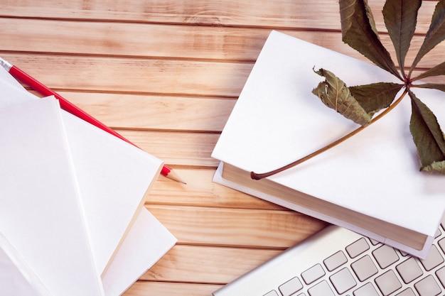 Pilha de livros brancos, teclado e lápis com folha de plátano