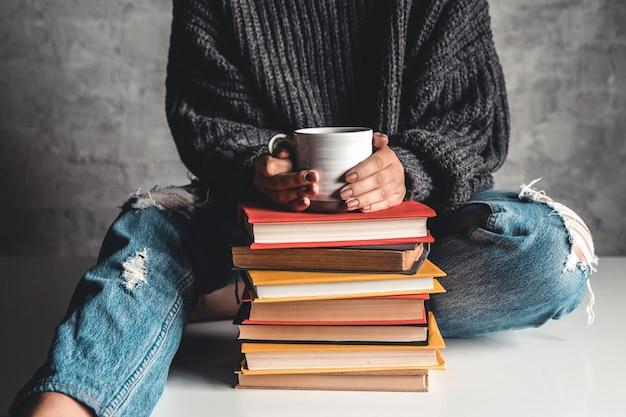 Pilha de livros com a caneca na frente do livro de leitura de uma mulher