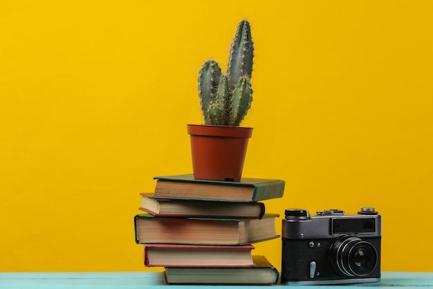 Pilha de livros com cacto e câmera em amarelo