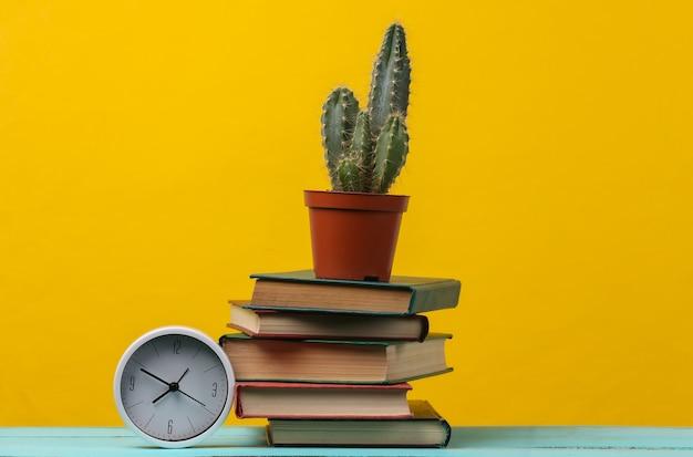 Pilha de livros com cacto e relógio amarelo