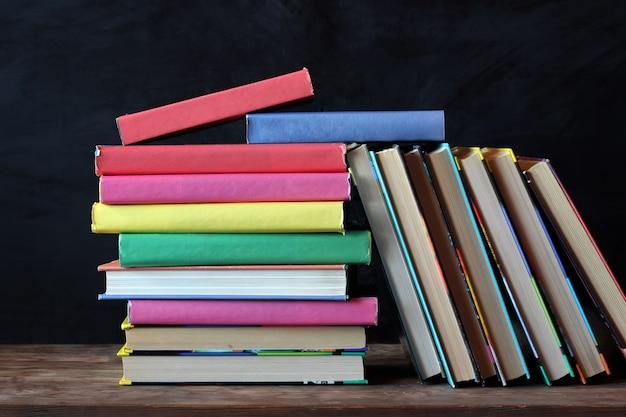 Pilha de livros com capas coloridas na mesa em frente a uma placa preta.