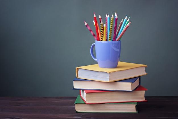 Pilha de livros com capas de cor e lápis de cor em um copo sobre uma mesa de madeira. uma natureza morta com livros.