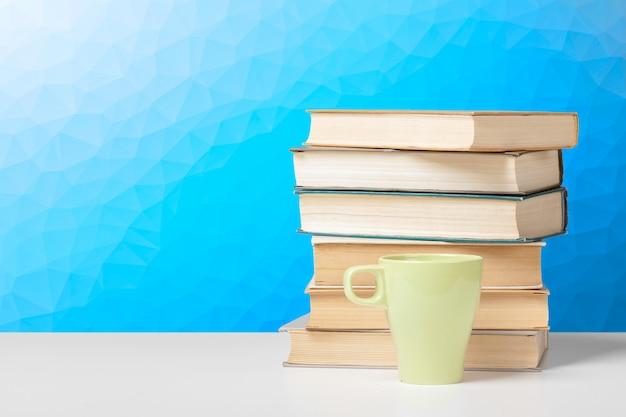 Pilha de livros com copo