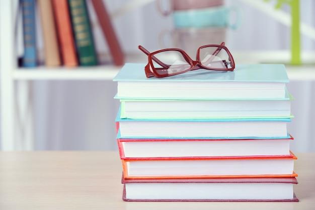 Pilha de livros com copos na mesa de madeira da sala