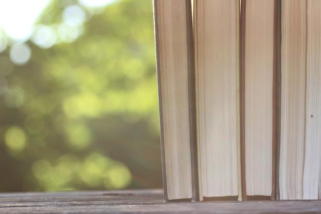 Pilha de livros com fundo de mesa de madeira ao ar livre