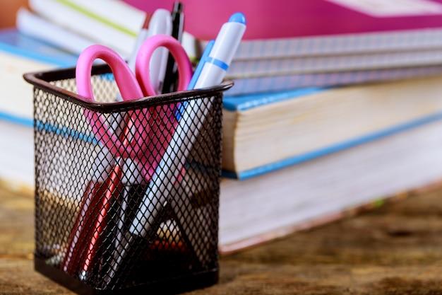Pilha de livros com lápis de cor, um fundo de madeira. material escolar com livros