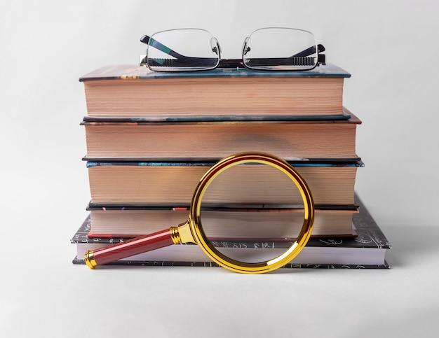 Pilha de livros com lupa e óculos em fundo branco.