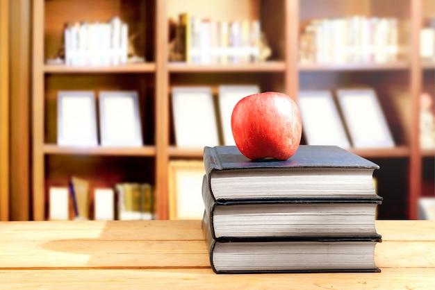 Pilha de livros com maçã na mesa de madeira na biblioteca