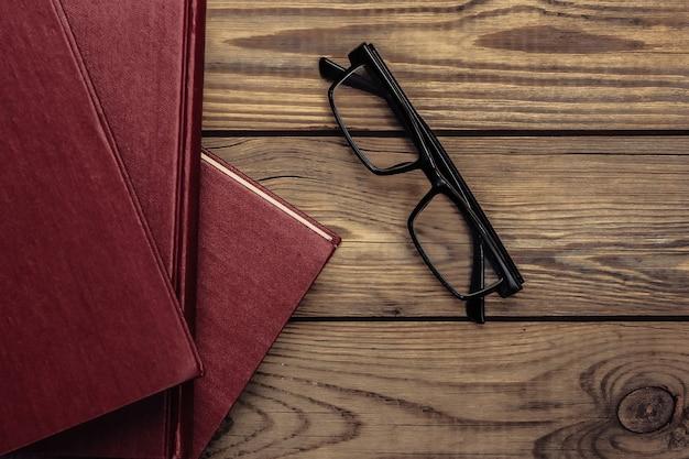 Pilha de livros com óculos em uma madeira. biblioteca, amante de livros