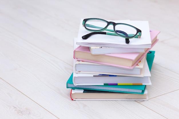 Pilha de livros com óculos no topo. causa do conceito de hipermetropia, miopia.