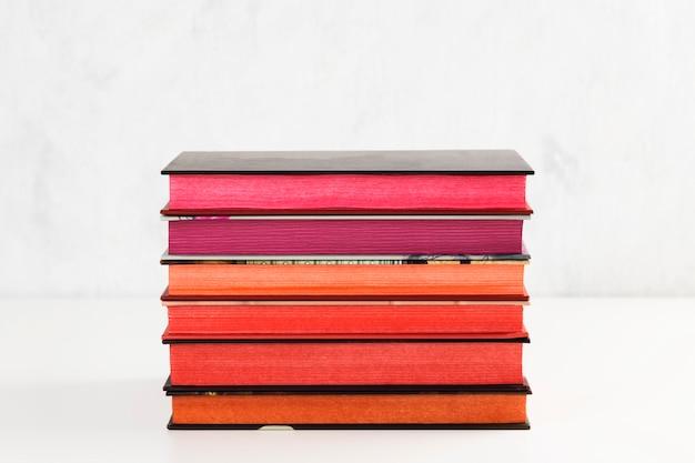 Pilha de livros com pilha de cores na mesa branca