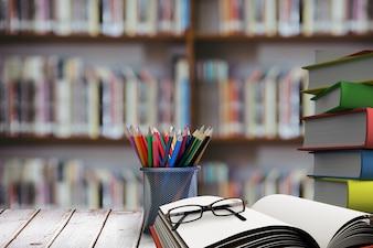 Pilha de livros com vidros na mesa de madeira