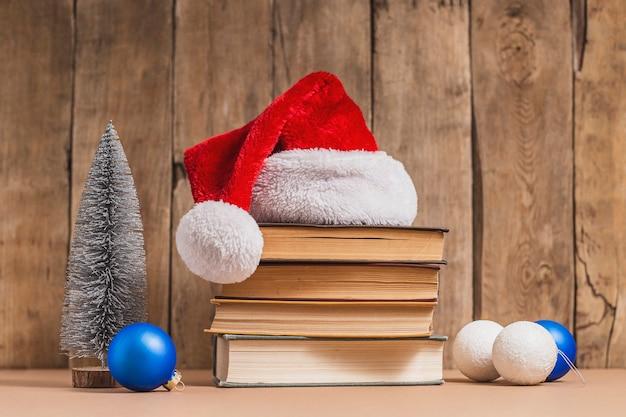 Pilha de livros, decorações de natal e chapéu de papai noel em fundo de madeira.