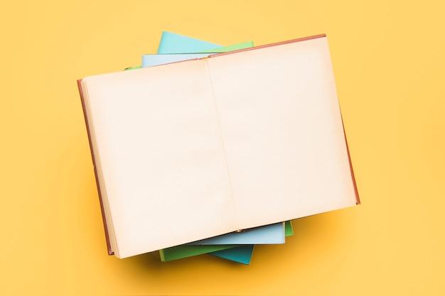 Pilha de livros e bloco de notas aberto com páginas em branco