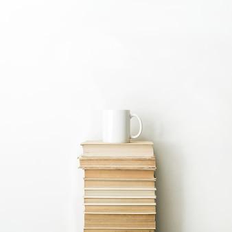 Pilha de livros e caneca de café na superfície branca