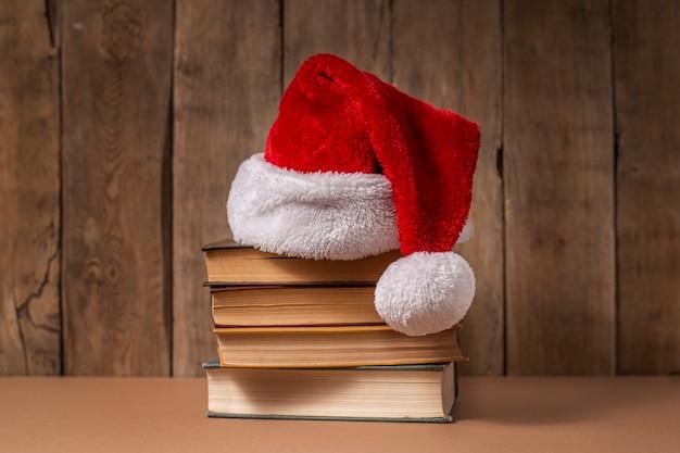 Pilha de livros e chapéu de papai noel em fundo de madeira.