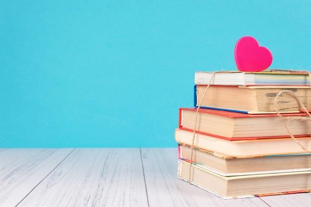 Pilha de livros e coração rosa