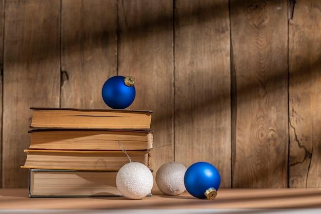 Pilha de livros e decorações para árvores de natal em fundo de madeira.