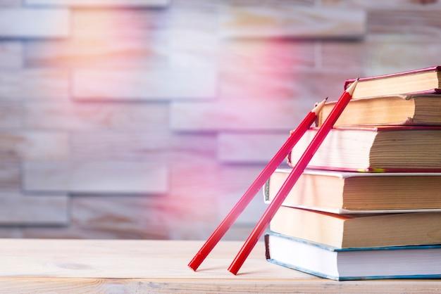Pilha de livros e dois lápis de madeira vermelhos na madeira, volta às aulas