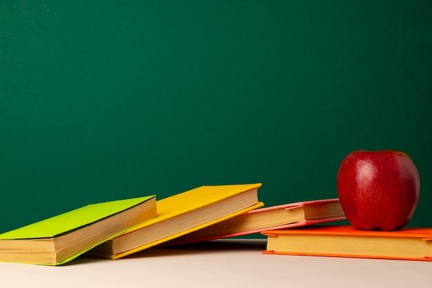Pilha de livros e maçã vermelha na mesa. conceito de volta às aulas