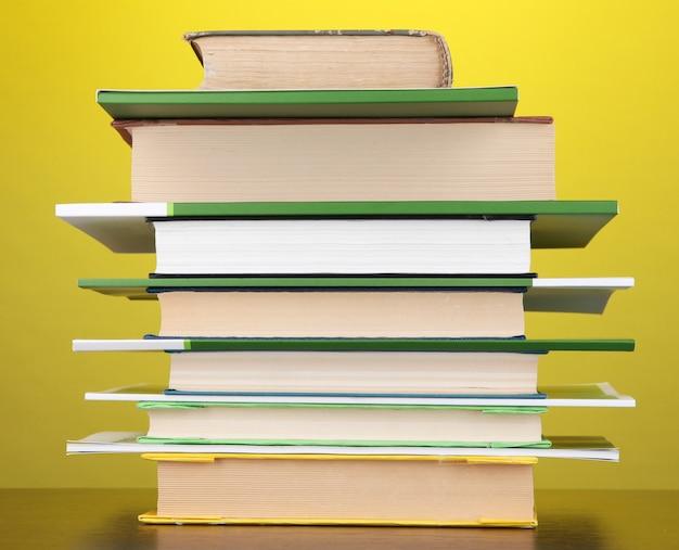 Pilha de livros e revistas interessantes na mesa de madeira em amarelo
