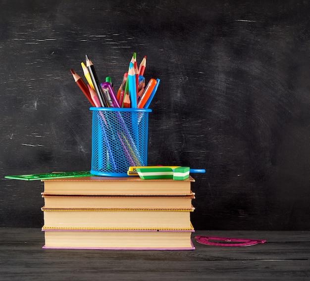 Pilha de livros e um copo azul de papelaria com lápis de madeira multi-coloridas