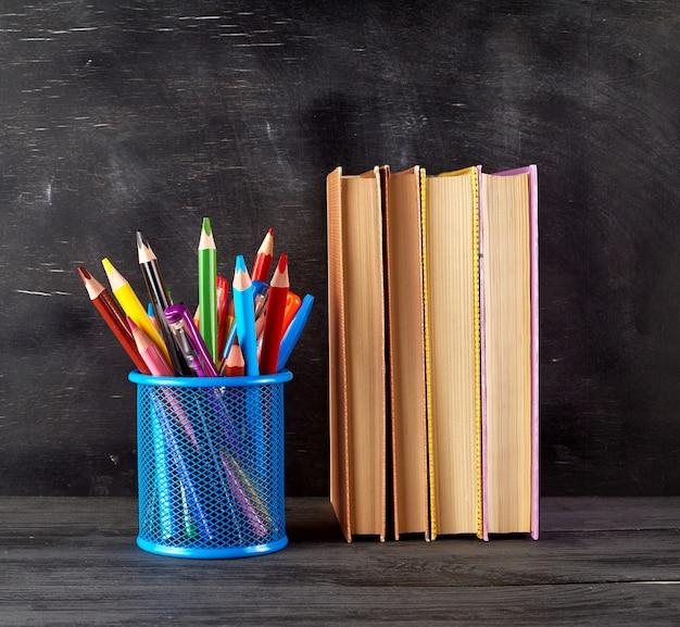 Pilha de livros e um copo de papelaria azul com lápis de madeira multi-coloridas