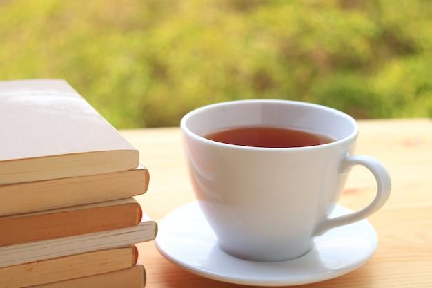 Pilha de livros e um copo do chá quente em uma tabela pela janela com fundo borrado da folhagem de outono.