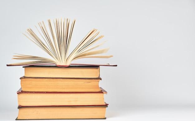Pilha de livros e um livro aberto com páginas amarelas