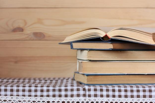 Pilha de livros e um livro aberto sobre a mesa. espaço vazio para o seu texto. biblioteca, lendo.