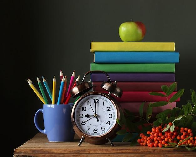 Pilha de livros em capas coloridas, lápis, despertador e um ramo de mountain ash em cima da mesa.
