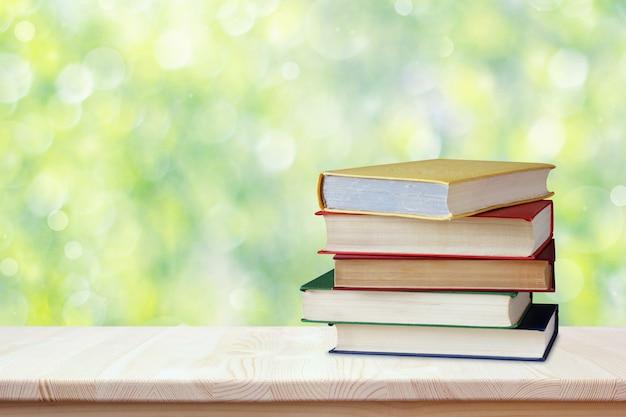 Pilha de livros em capas de cor em cima da mesa. local de trabalho do aluno.